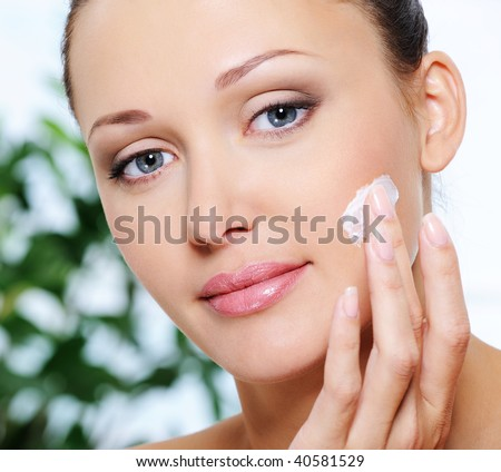 Close-up portrait of beautiful woman caring of her face - stock photo