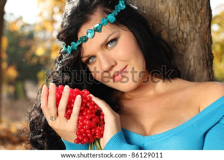 Close-up portrait of beautiful woman in blue with red arrow-wood, outdoors - stock photo