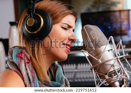 Close-up portrait of beautiful woman in headphones singing - stock photo