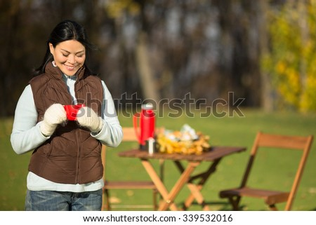 Close-up portrait of beautiful woman smiling and holding a red cup of hot tea on a picnic. The wooden table is on the background. - stock photo