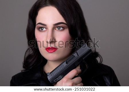 close up portrait of beautiful woman with gun over grey background - stock photo