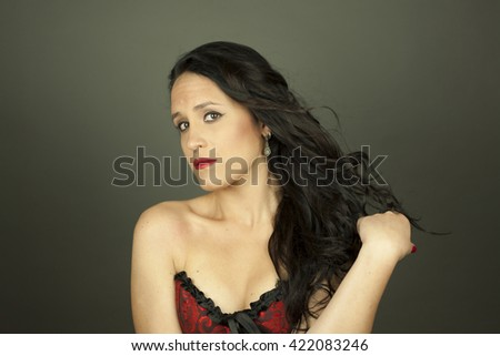 Close up portrait of beautiful woman with hair motion shoot in studio, isolated on a grey background