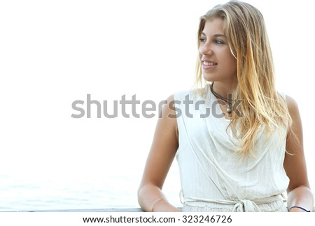 Close up portrait of beautiful young adolescent blond girl in a coastal beach destination, leaning relaxing and smiling on a sunny vacation, summer holiday. Healthy and well being lifestyle, outdoors. - stock photo