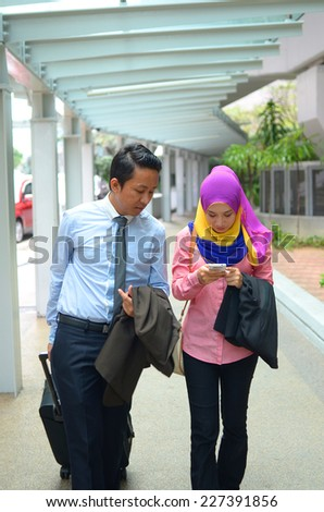 Close-up portrait of beautiful young Asian businesswomen and businessman discuss together - stock photo