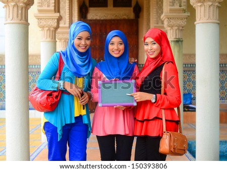 Close-up portrait of beautiful young Asian student together with green board - stock photo