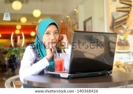 Close-up portrait of beautiful young Asian student with laptop - stock photo