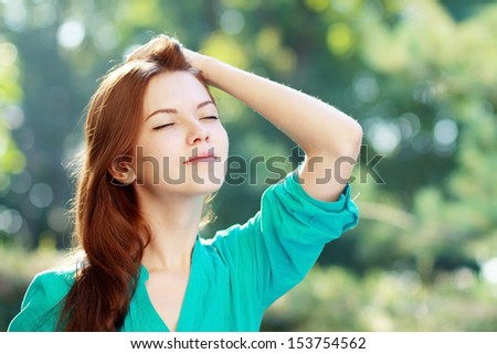 close-up portrait of beautiful young blond woman in white blouse at park holding her head enjoying fresh air - stock photo