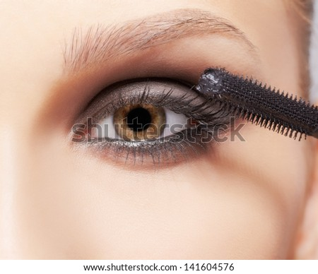 close-up portrait of beautiful young brunette woman applying mascara for eyelash extension - stock photo