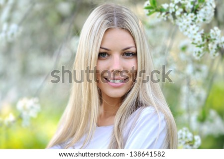 Close-up portrait of  beautiful young fashion model posing outdoor in sunny green park - stock photo