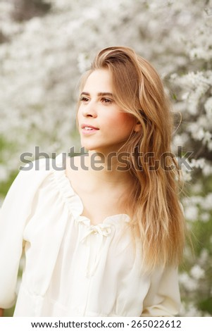 close up portrait of beautiful young girl in  blossom garden on a spring day - stock photo