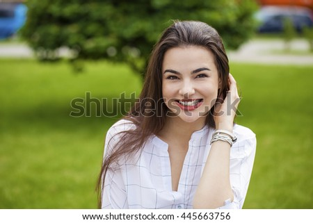 Close up portrait of beautiful young happy brunette woman with fresh and clean skin, summer street outdoors - stock photo
