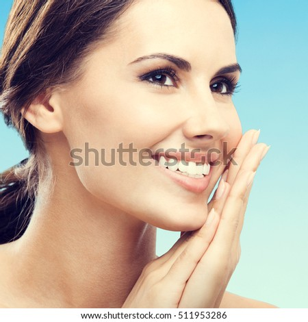 Close up portrait of beautiful young happy smiling woman, over blue background