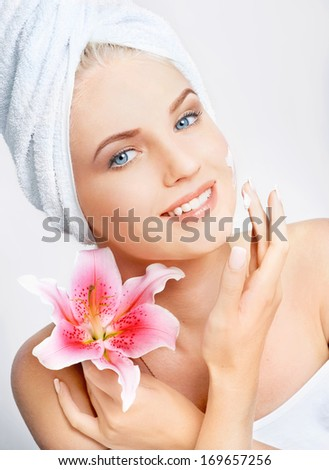 Close-up portrait of beautiful young smiling girl with flower on light gray background. Spa treatments - stock photo