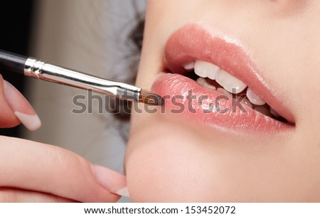 close up portrait of beautiful young woman applying lips makeup with cosmetic brush