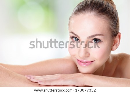 Close up portrait of beautiful young woman face while lying. Isolated on green background. Skin care or spa concept