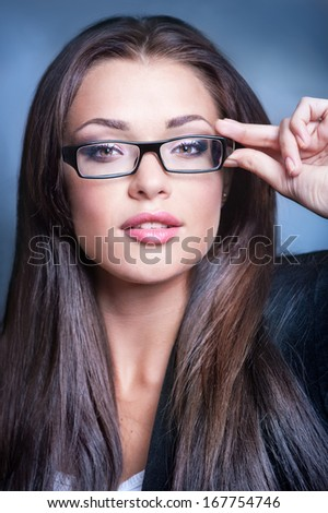 Close-up portrait of beautiful young woman in glasses on dark blue background