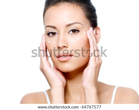 Close-up portrait of beautiful young woman's face with point of rejuvenating cream under the eyes - isolated - stock photo