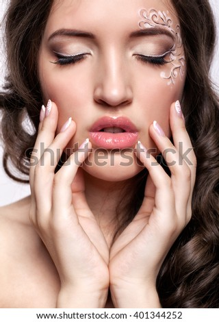 Close-up portrait of beautiful young woman with closed eyes,  face art  make up and manicure