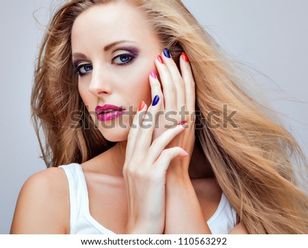 Close-up portrait of beautiful young women with multicolored make-up. - stock photo