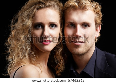 close-up portrait of blonde couple on black - stock photo