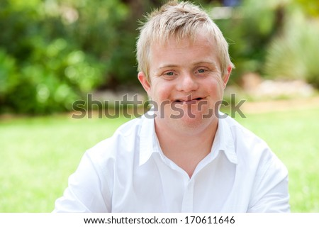 Close up portrait of boy with down syndrome in white shirt outdoors. - stock photo
