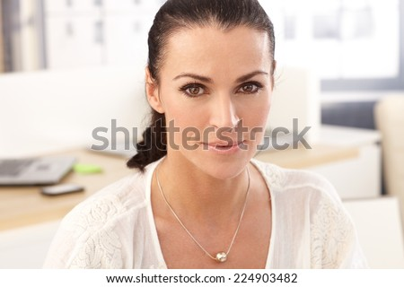 Close up portrait of brunette, casual, smiling businesswoman at work office. - stock photo