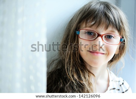 Close-up portrait of brunette child girl in glasses