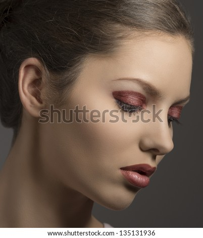 close-up portrait of brunette female with red glossy make-up turned of three quarters on gray background - stock photo