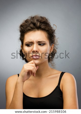 close-up portrait of brunette thoughtful young woman looking down - stock photo
