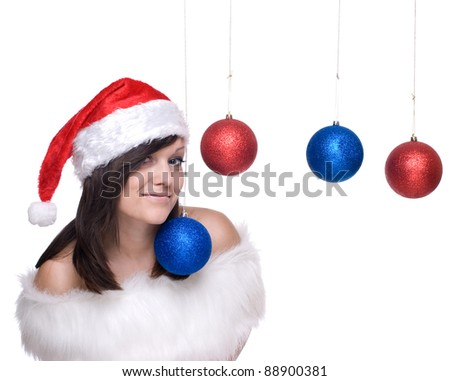 Close up portrait of brunette woman in santa claus dress, white fur playing with decoration balls