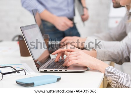 Close-up portrait of business people using laptop computers in office. Internet technologies and business projects concepts.