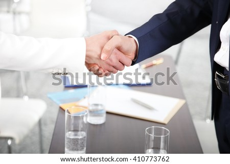 Close-up portrait of businesswoman and businessman shaking hands after business meeting.