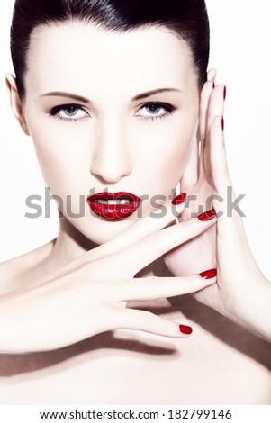 close-up portrait of caucasian brunette wearing red lipstick, spot lighting - stock photo