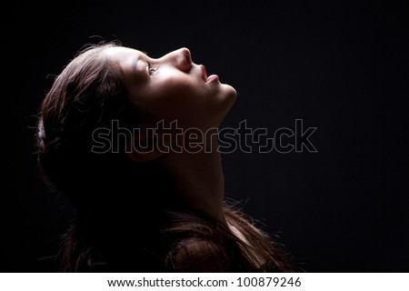 Close up portrait of charming young girl lasting up to light on black background - stock photo