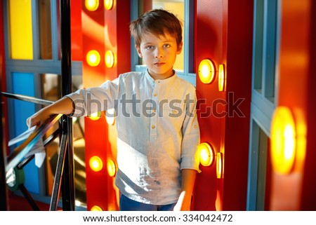 Close-up portrait of cheerful little boy indoors on playground - stock photo