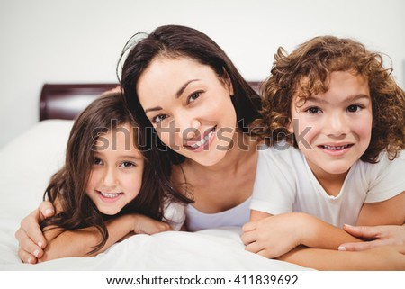 Close-up portrait of cheerful woman with children lying on bed at home - stock photo