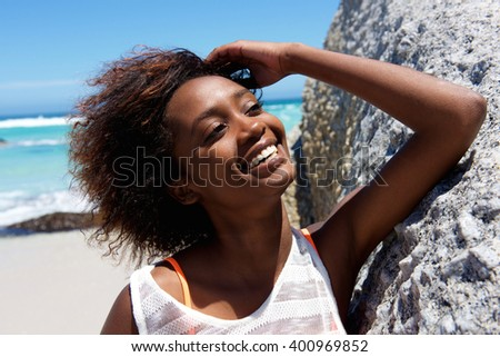 Close up portrait of cheerful young african american woman outdoors at the beach - stock photo