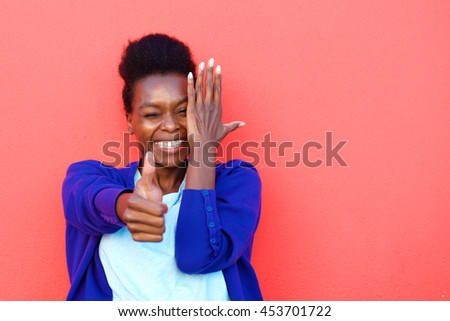 Close up portrait of cheerful young african woman showing thumbs up sign against red background - stock photo
