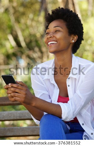 Close up portrait of cheerful young woman sitting on a bench outdoors holding a mobile phone