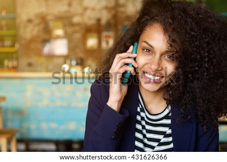 Close up portrait of cheerful young woman talking on mobile phone at cafe and smiling - stock photo