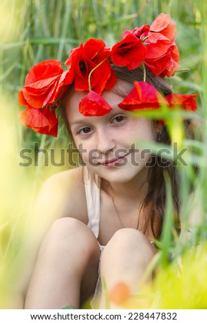 close up portrait of child girl with circlet of poppies sitting at the grass