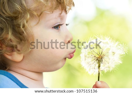 Close-up portrait of child with dandelion on sunny-green background - stock photo
