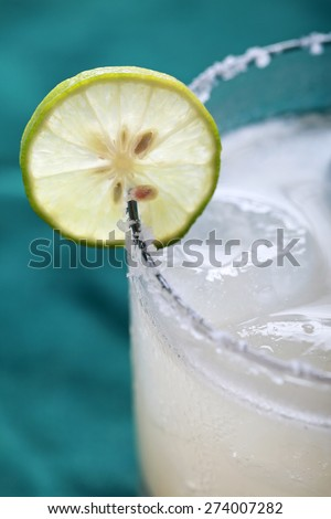 close up portrait of Classic margarita cocktail with lime and salty rim - stock photo