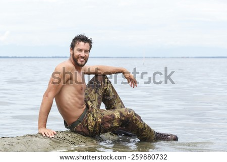 Close up Portrait of Confident  Athletic Army with No Shirt Posing at the Beach With no Shirt - stock photo
