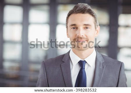 Close-up portrait of confident handsome businessman in office - stock photo