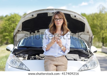 Close-up portrait of confident middle aged woman using her mobile phone while standing on the road at her broken down car. - stock photo