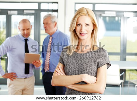 Close-up portrait of confident sales woman standing at office while her colleagues consulting at background. Business meeting  - stock photo