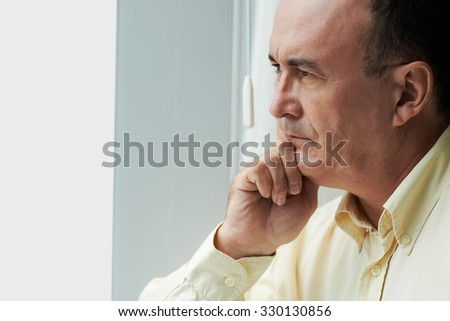 Close-up portrait of contemplating mature man looking through the window