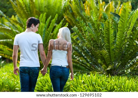 Close up portrait of couple enjoying romantic walk in park. - stock photo
