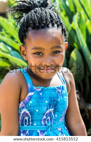 Close up portrait of cute african girl in blue dress and braided hairstyle outdoors.